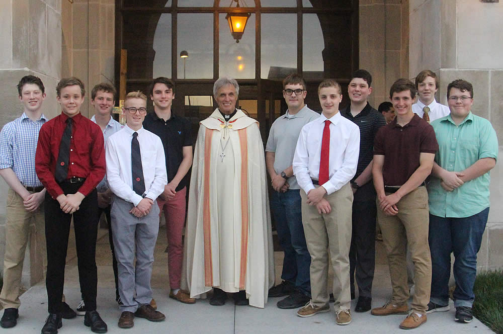 Abbot Michael poses with new student oblates in front of the DJ Sokol Chapel at Mount Michael Benedictine School