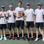 Photo of team with medals and championship plaque